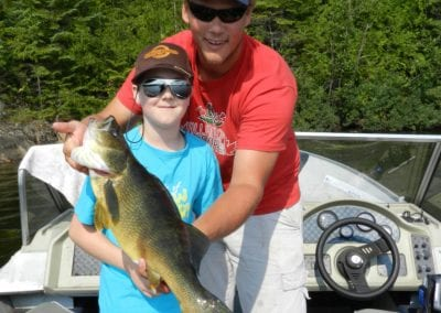 Young fisherman with great walleye in ontario and guide Jake